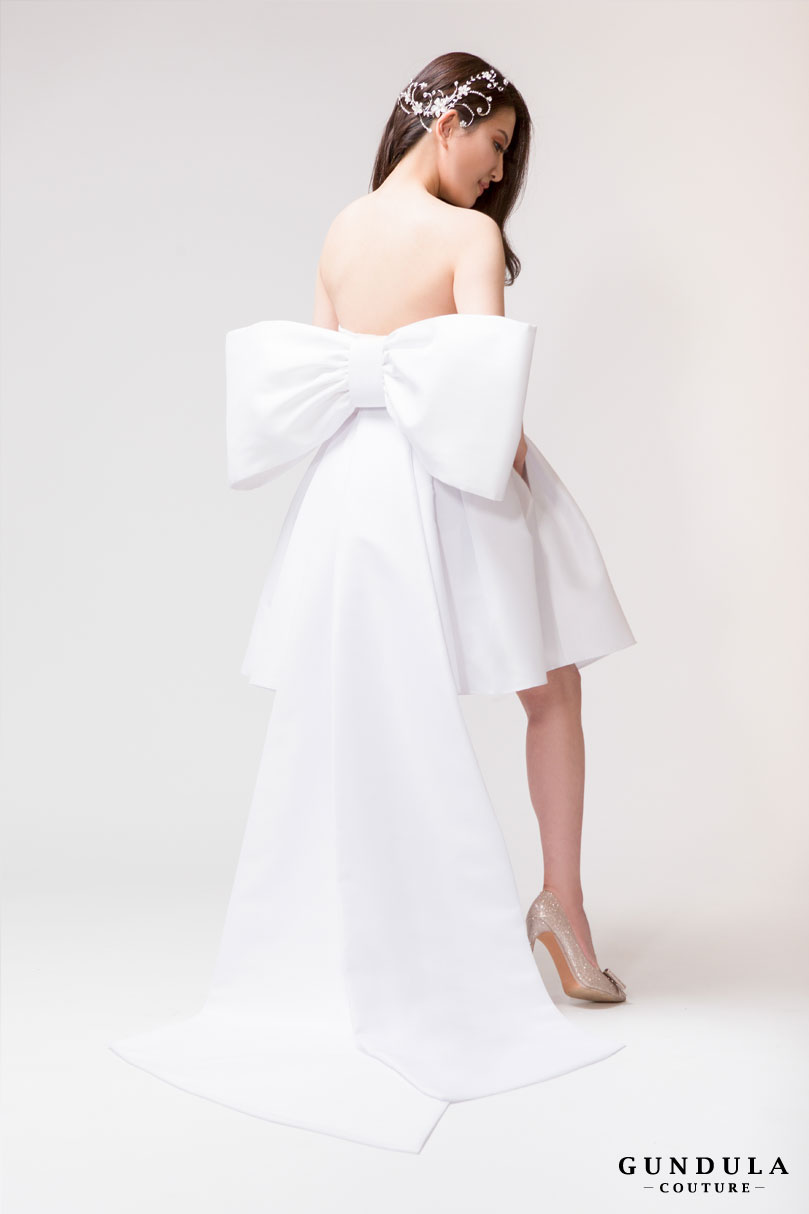 An image of the back of a Gundula Couture dress with large bow at back.